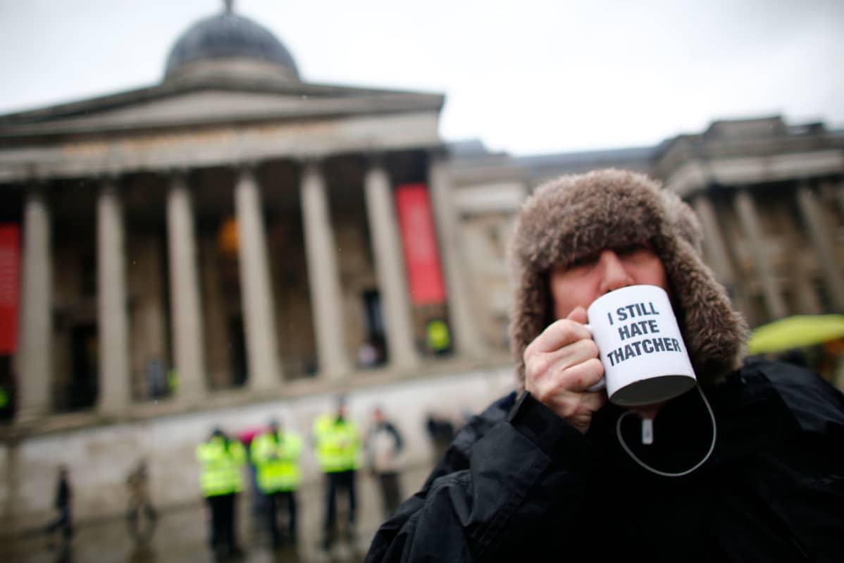 """Kuva mielenosoittajasta, joka juo kupista jossa lukee """"I still hate Thatcher""""."""