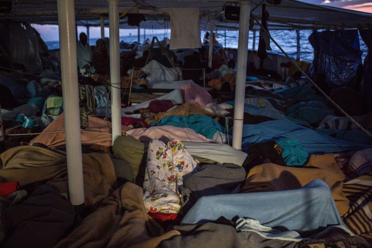Matkustajat nukkuvat kannella