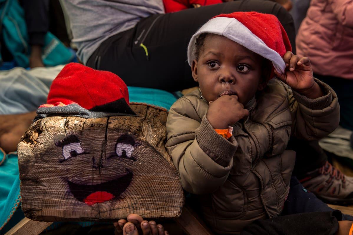 Lapsi leikkii jouluhalon ja tonttulakin kanssa