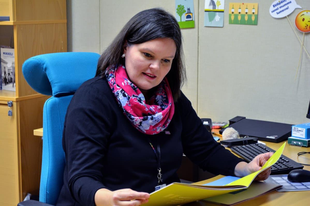 Heidi Hänninen työpöytänsä ääressä selailee esitettä.