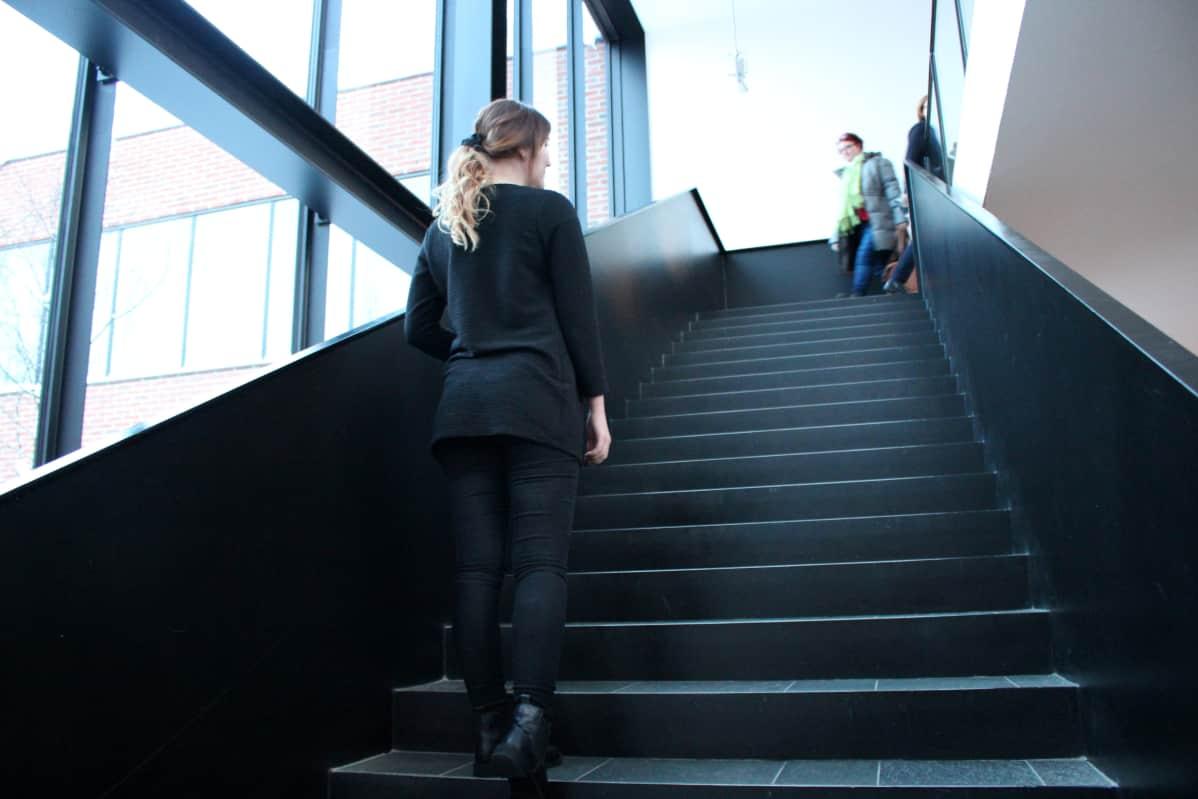 Nuori opiskelija nousee portaita ylös.