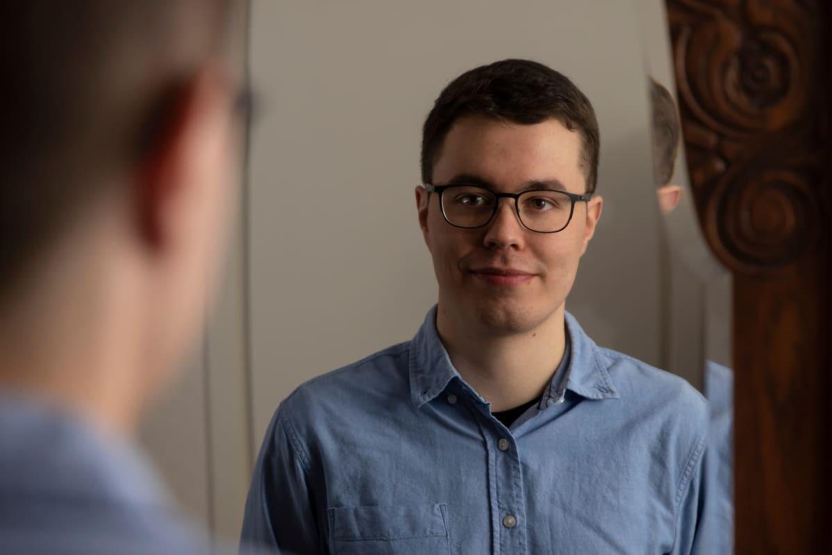 Nuori mies katsoo peilin kautta itseään