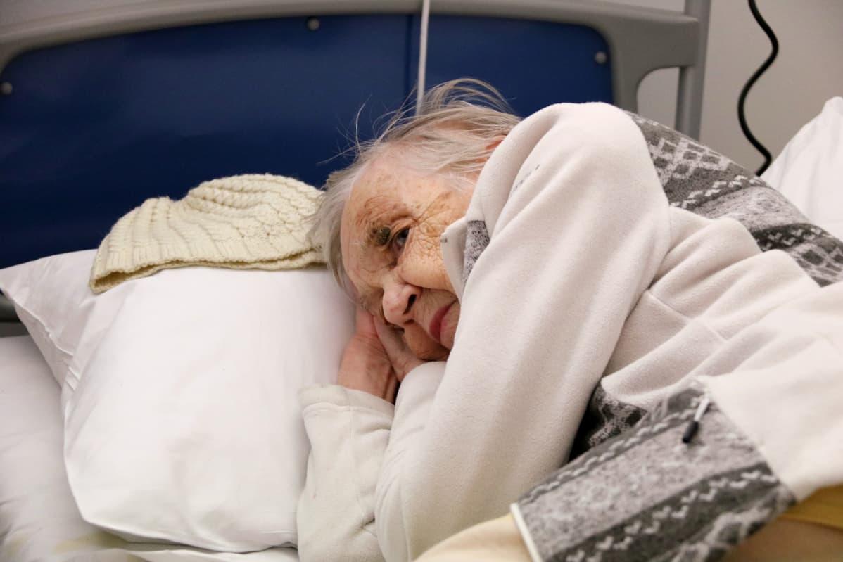 Iäkäs nainen lepää sairaalavuoteella.