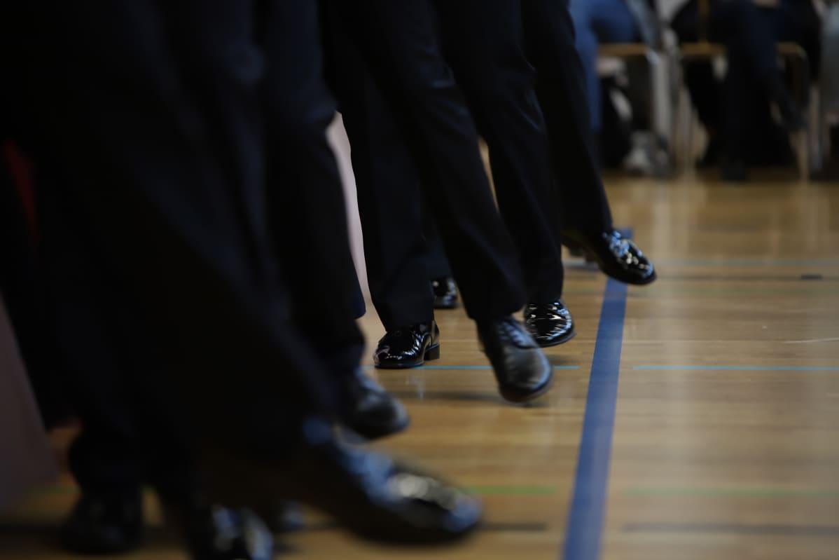 Poikien jalkoja tanssiessa.
