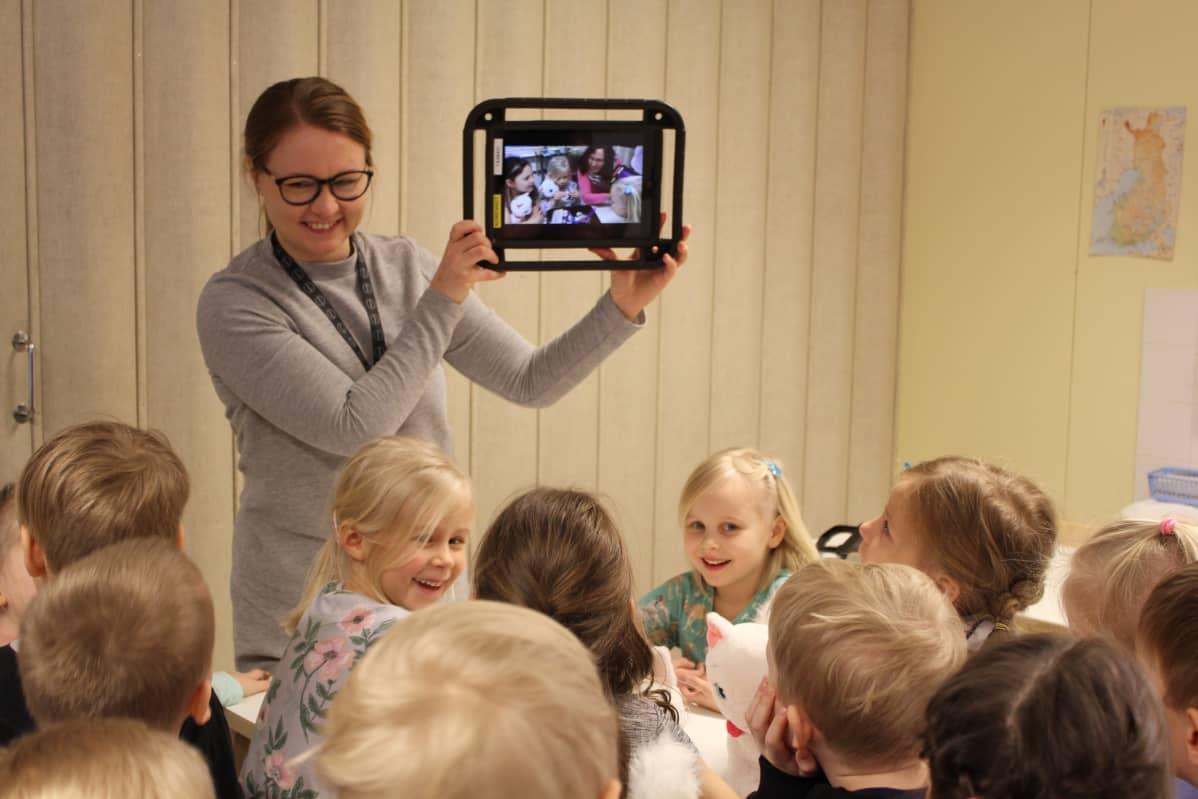Kotkan varhaiskasvatuksen kehittämiskoordinaattori Tiina Kääpä näyttää lapsille näiden keksimää tarinaa tabletin näytöltä.