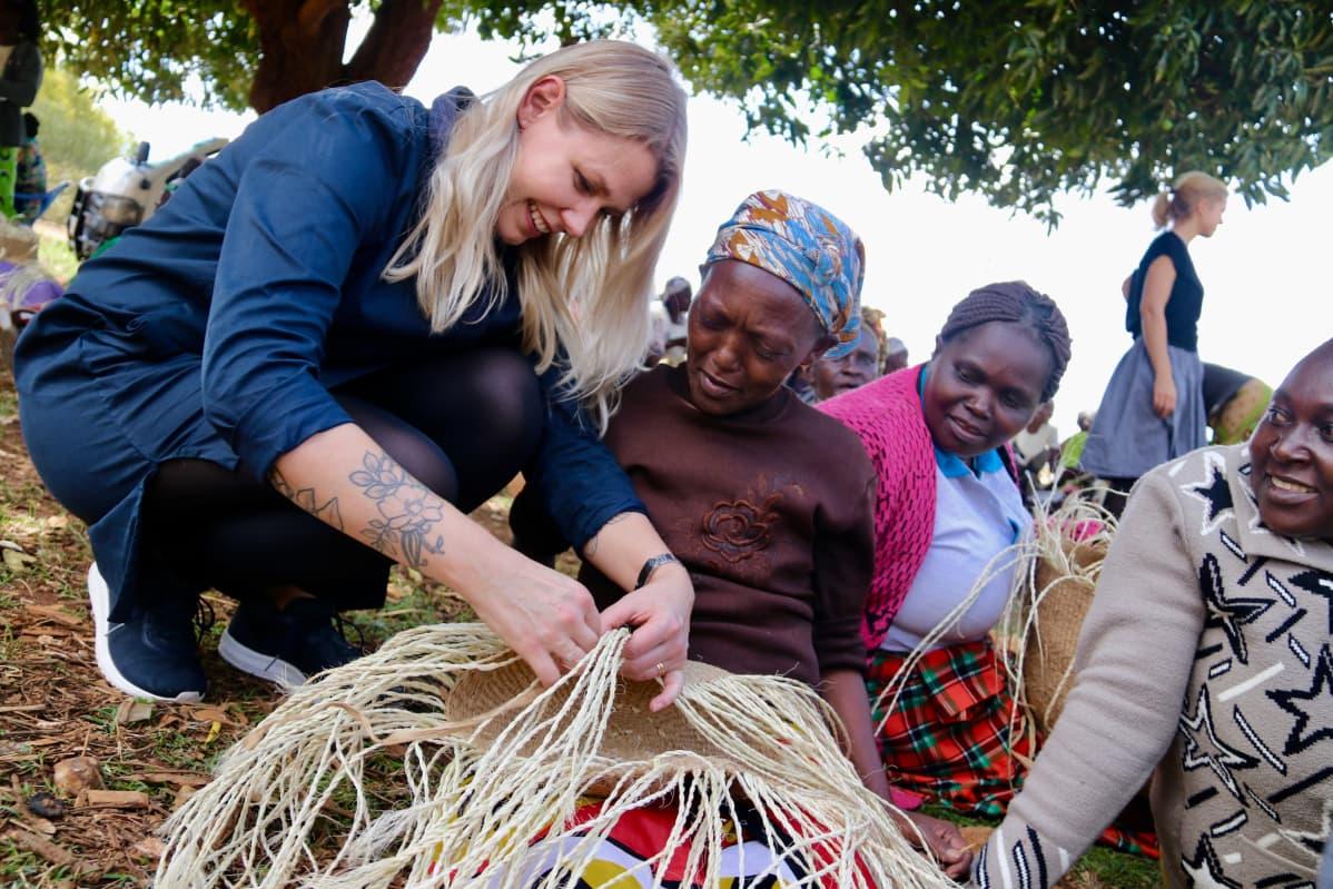 Vaaleahiuksinen, siniseen pukeutunut nainen punoo koria