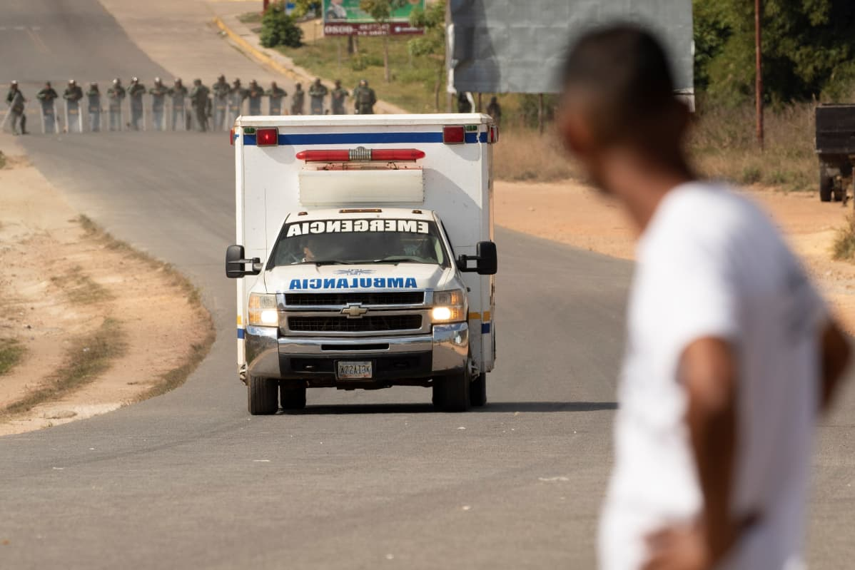 Ambulanssi poistui Venezuelan rajalta kohti Pacairaman kaupunkia Brasiliassa lauantaina. Ainakin kaksi ihmistä kuoli ja kymmeniä loukkaantui, kun Venezuelan kansalliskaarti pysäytti opposition kannattajat, jotka yrittivät saada avustuskuormia maahan.
