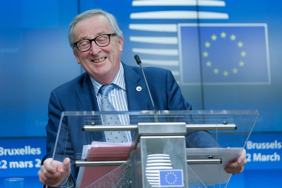 Juncker nauraa silmät kiinni.