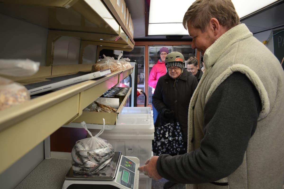 Kalastaja Jukka Toivonen punnitsee suosittuja silakoita kauppa-autossa.