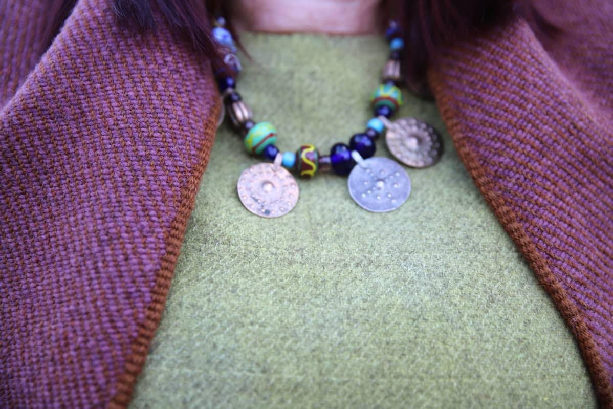 Yksityiskohta Mervi Pasasen puvusta.  Kuvassa kaulakoru, jossa kolikoita ja helmiä.