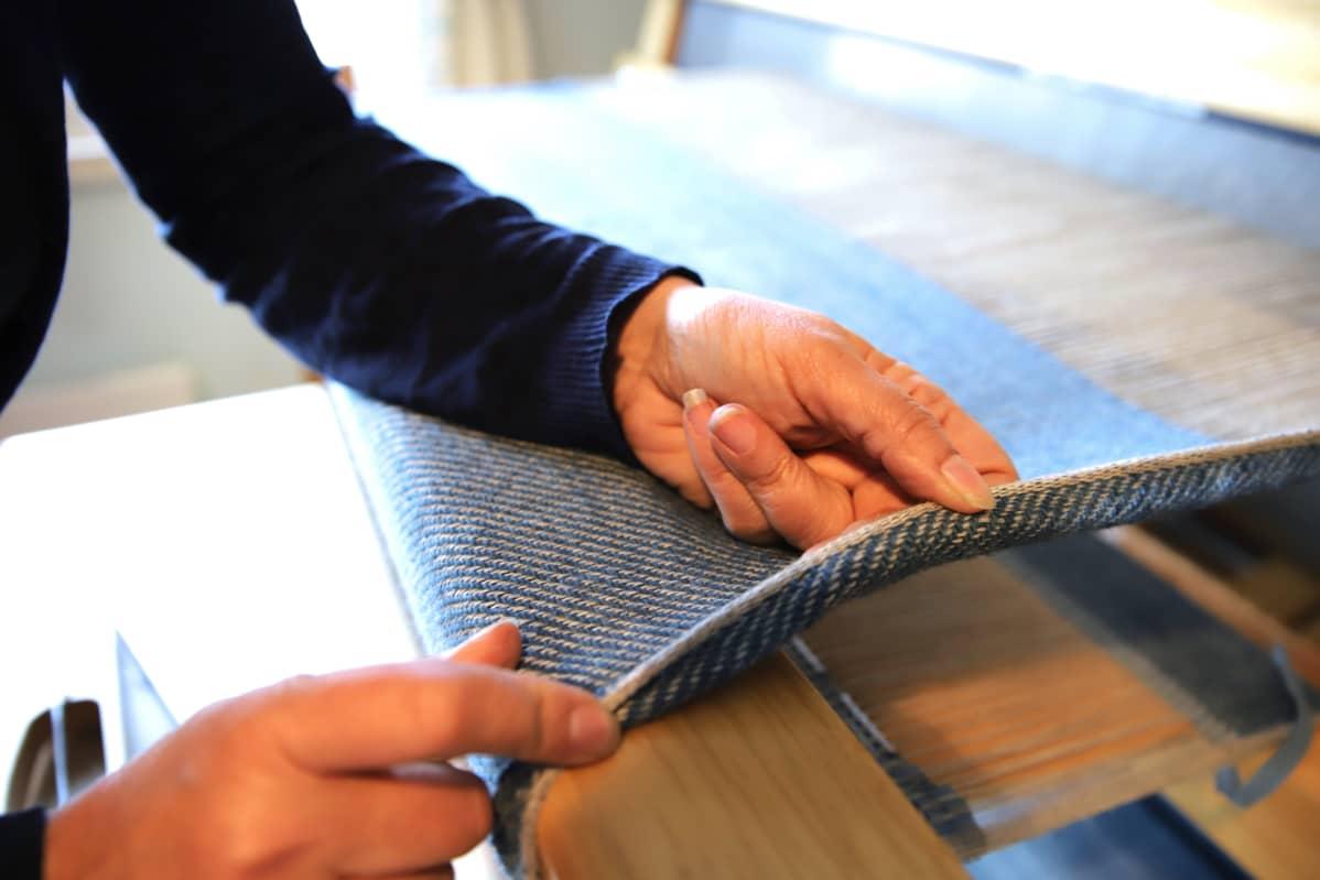 Mervi Pasanen esittelee kangasta, jota hän työstää kangaspuilla.