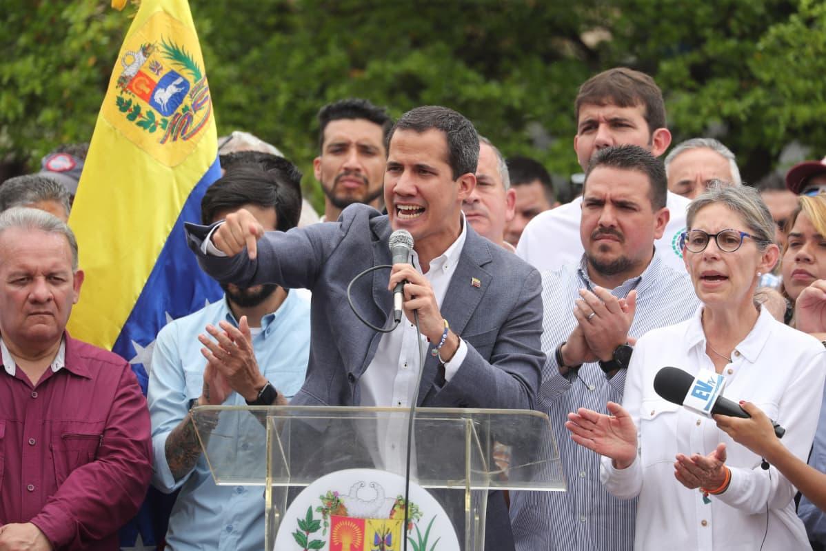 Juan Guaidó puhuu taustallaan kannattajia ja Venezuelan lippu.