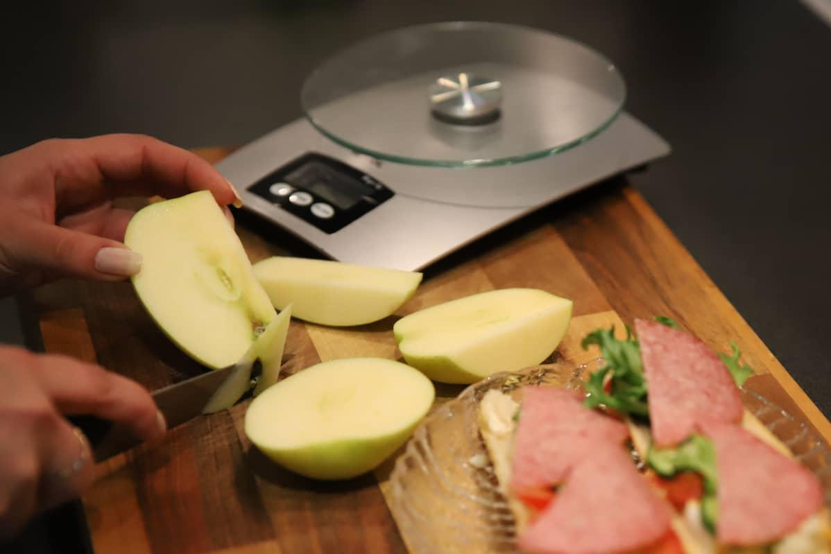 Nainen leikkaa omenaa, vieressä elintarvikevaaka.