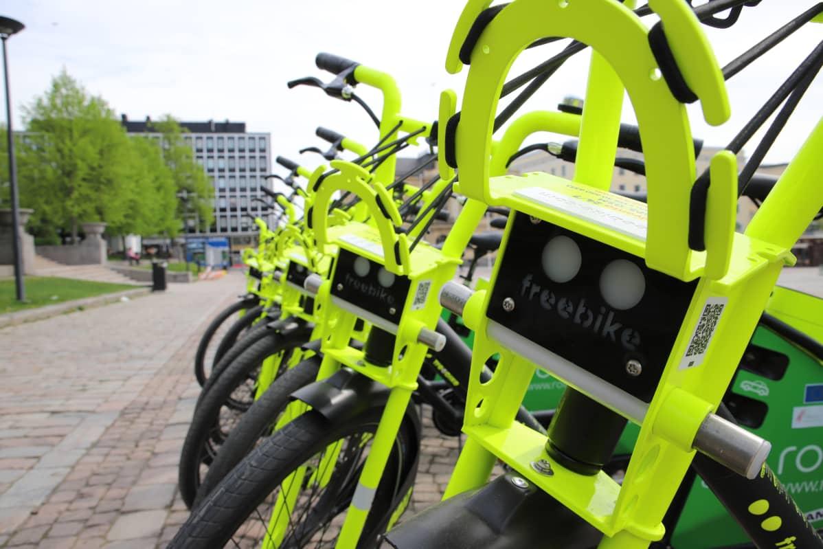 Rivissä neonvärisiä sähköpyöriä Hämeenlinnan torilla.
