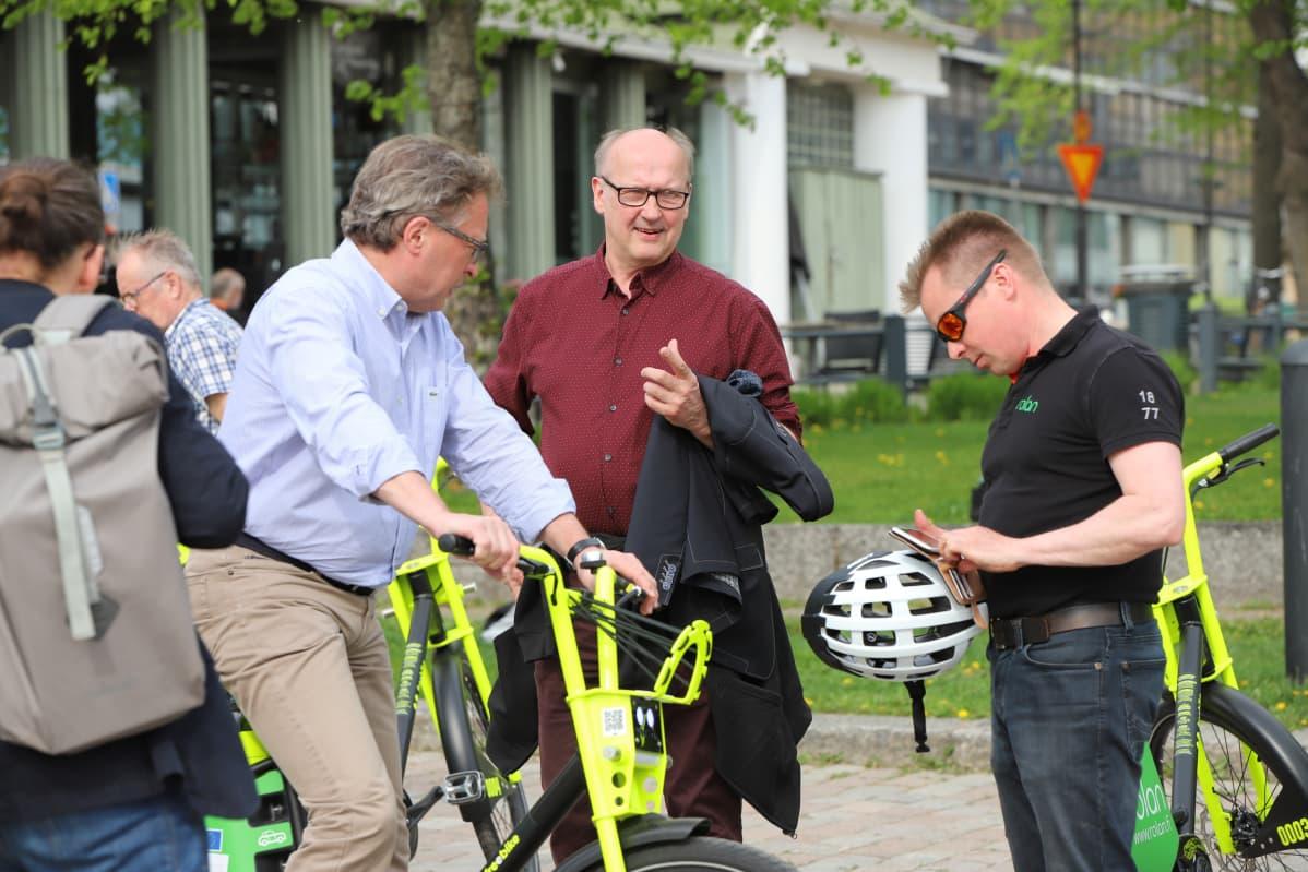 Kolme miestä tutkii, miten sähköpyörää käytetään.