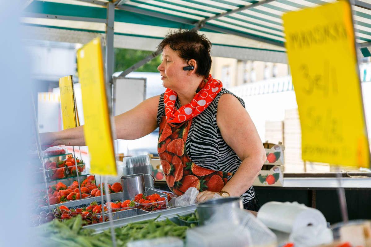 Nainen ojentaa kätensä myydessään mansikoita Turun kauppatorilla.
