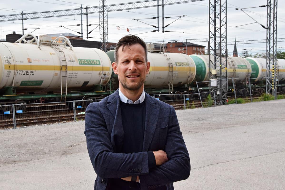 Mies seisoo junavaunun edessä.