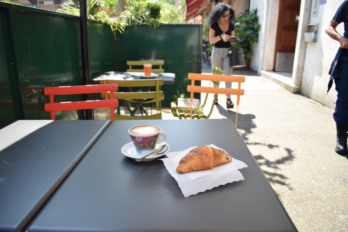 Maitokahvi ja leipomus terassipöydällä.