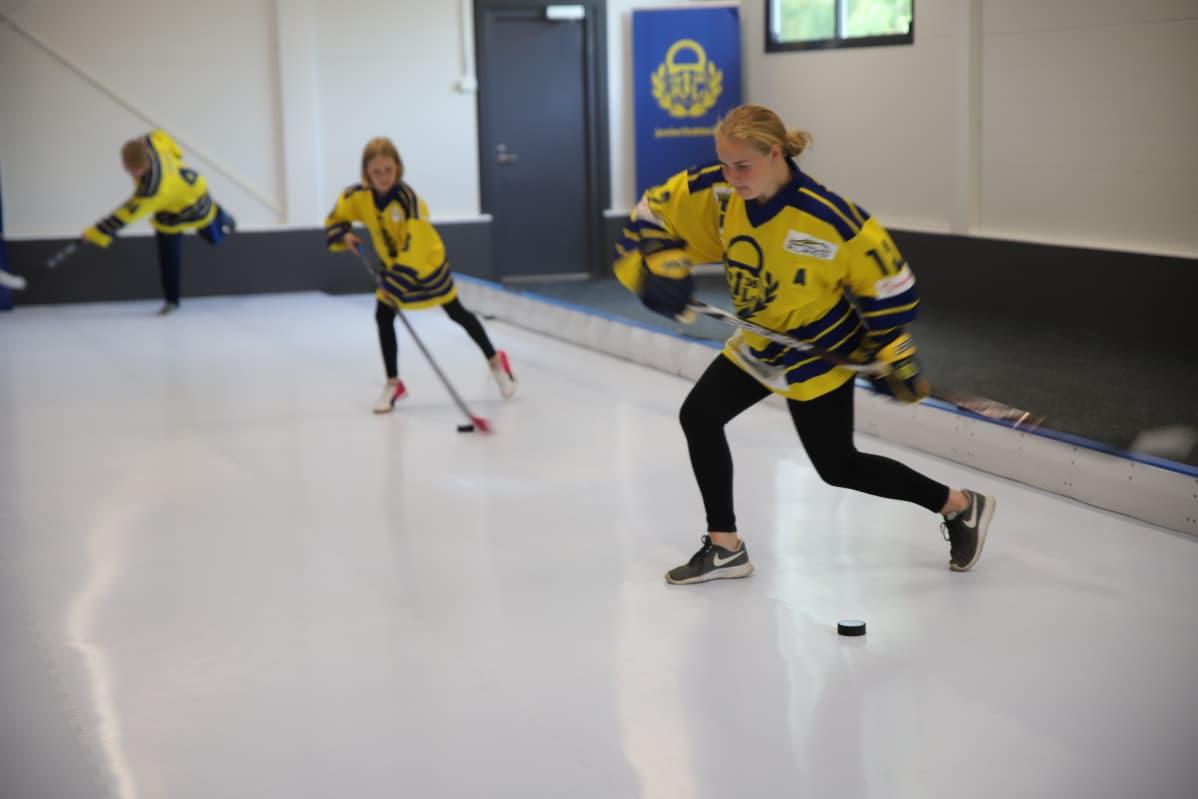 Kolme jääkiekkoilijaa laukoo kiekkoa Rauman laukaisuhallissa