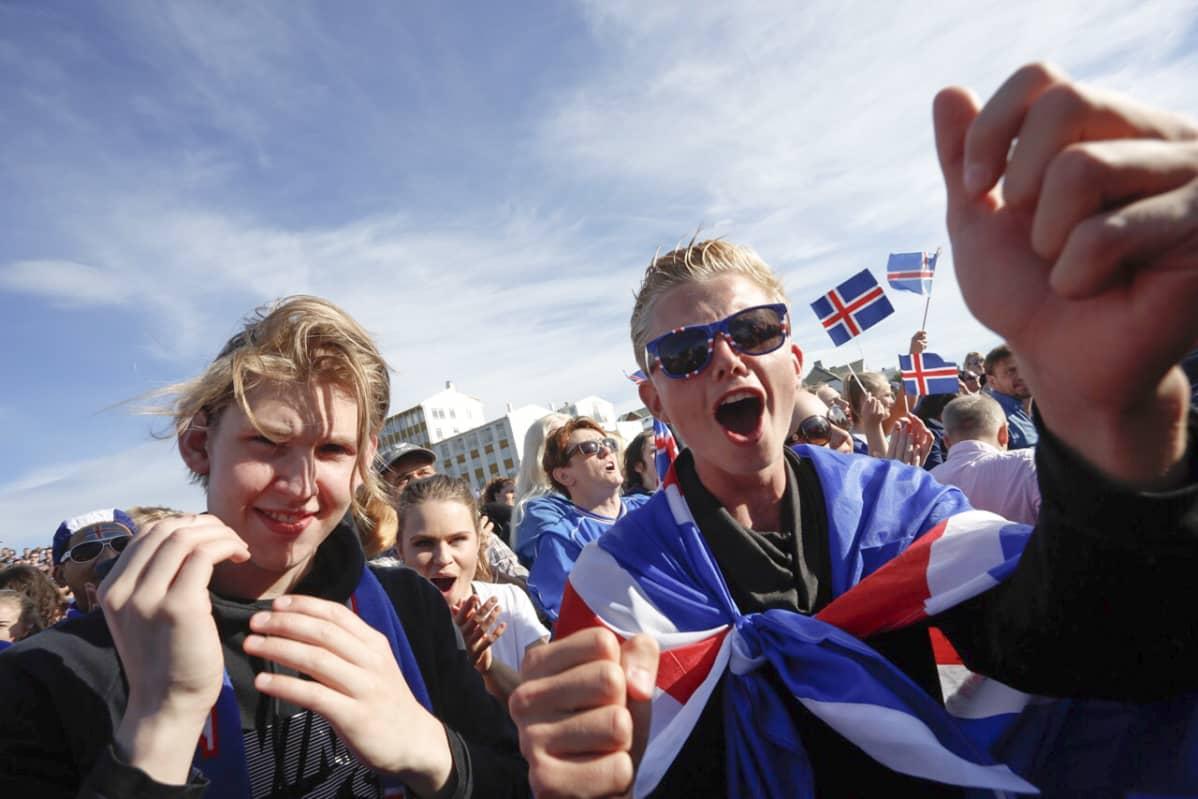 Islantilaisia nuoria ja aikuisia hurraamassa Islannin jalkapallojoukkueelle.
