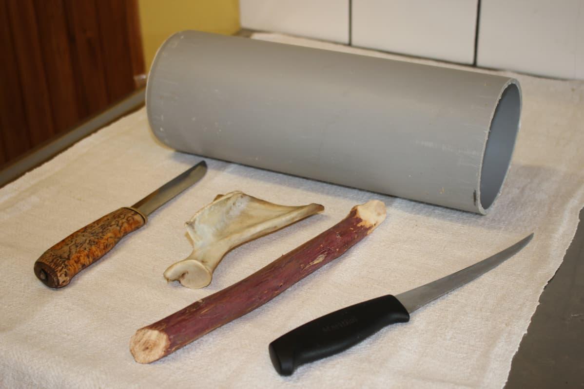 Pöydällä liinan päällä puukko, lusa, keppi, veitsi ja putkenpätkä.