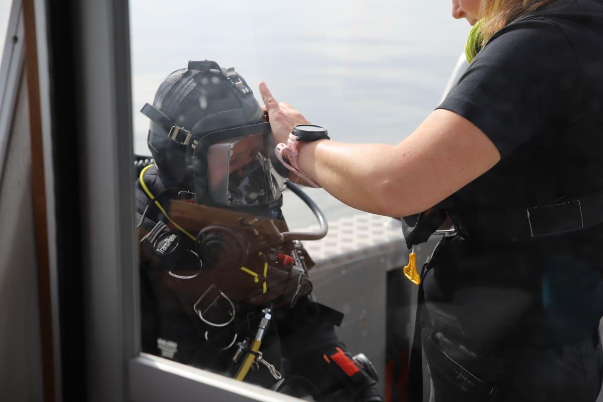 Päivi Pihlanjärvelle autetaan sukelluslaitteet päälle.