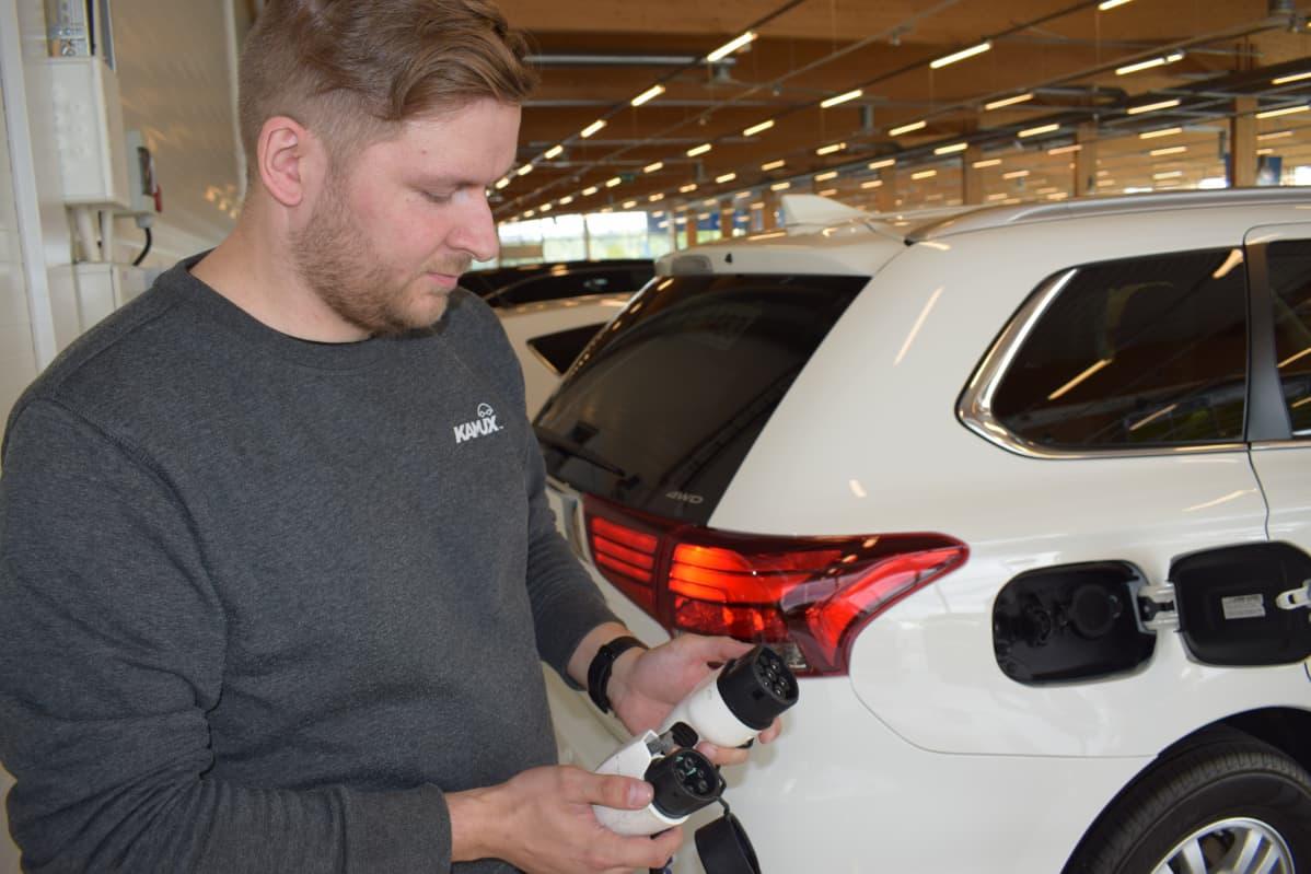 Automyyjä Petteri Mäkeläinen Kamuxilta esittelee kahta erilaista latausjohdon päätä.