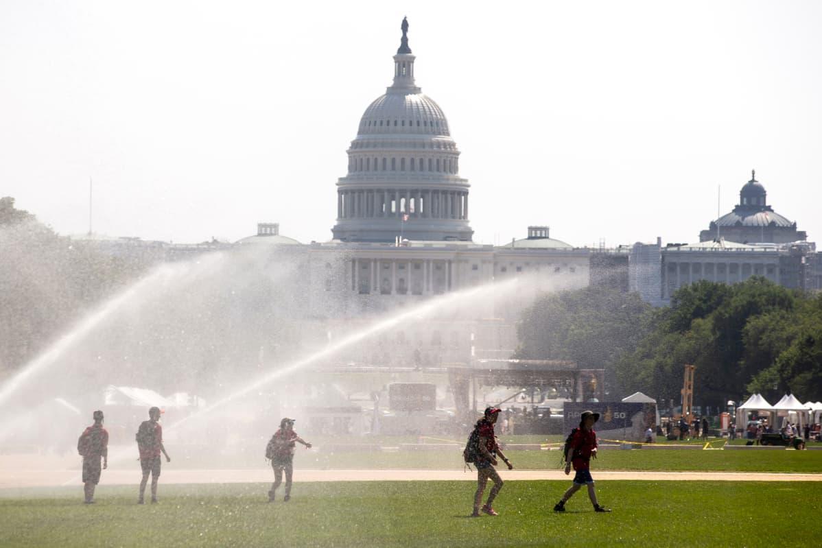 Nuoret kulkivat sprinklerien vesisuihkujen alla Washington DC:ssä 19. heinäkuuta.