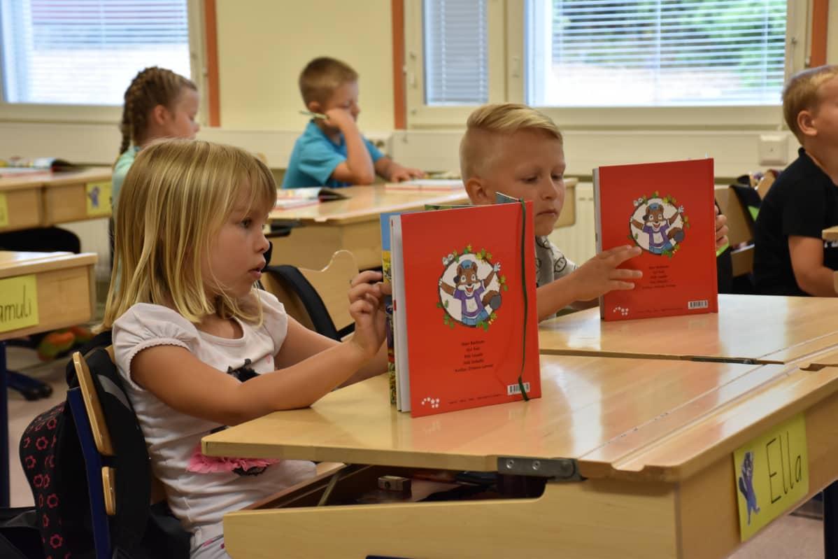 Ella Lampinen ja Lukas Kaasalainen selailivat uusia kirjojaan innokkaasti.