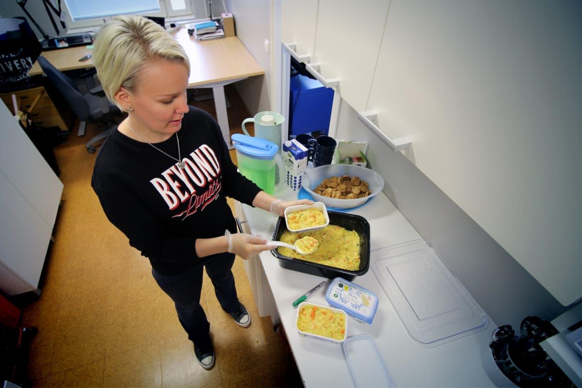 Nuoriso-ohjaaja Sari Paavonsalo siirtää Joroisten yhtenäiskoulun ruokalasta jäänyttä ylijäämäruokaa pienempiin rasioihin.