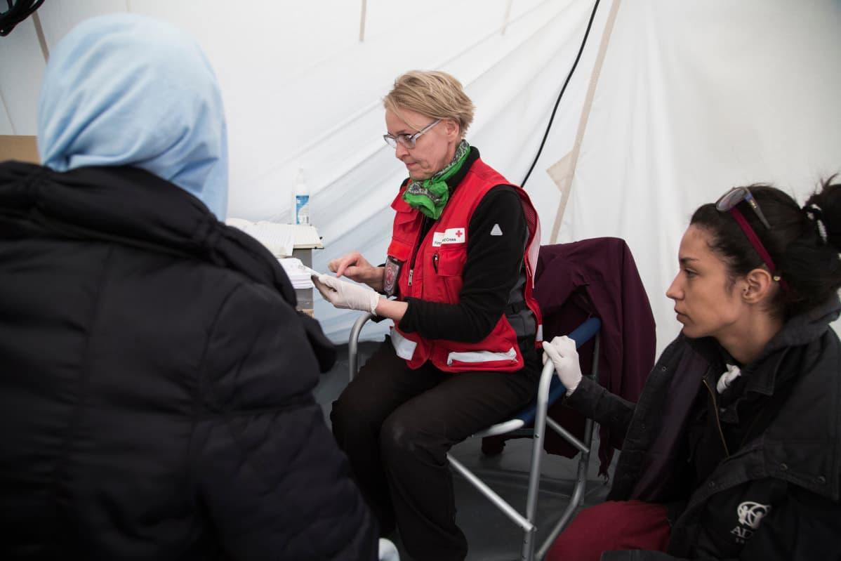 Kätilö Arja Savolainen hoitaa naisia klinikalla Nea Kavalan pakolaisleirillä Pohjois-Kreikassa. Kuva on vuodelta 2016.