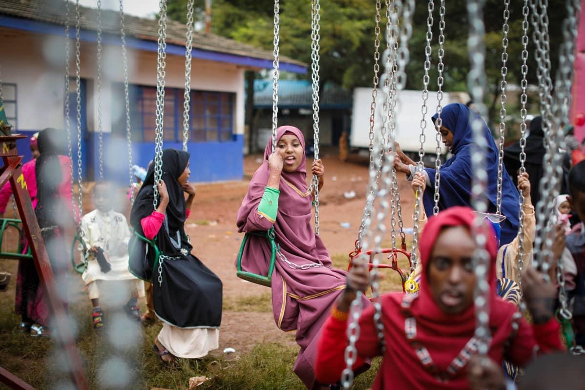 Tytöt kokeilevat keinuja nairobilaisen koulun pihalla kesäkuussa 2019. Maaseudulla monen tytön koulutaival katkeaa kuukautisten alkamiseen.