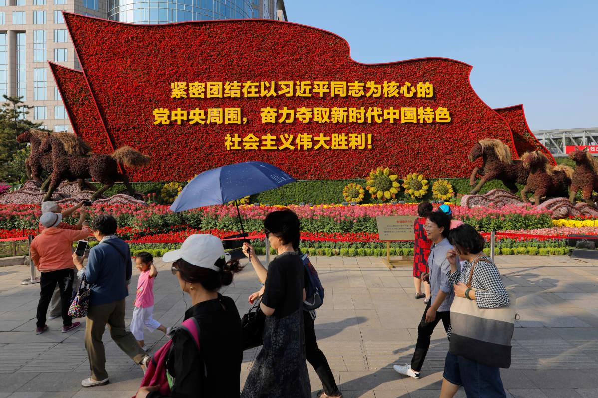 Kukilla koristeltu monumentti julistaa Xi Jinpingin ja kommunismin merkitystä juhlahumun alla Pekingissä.