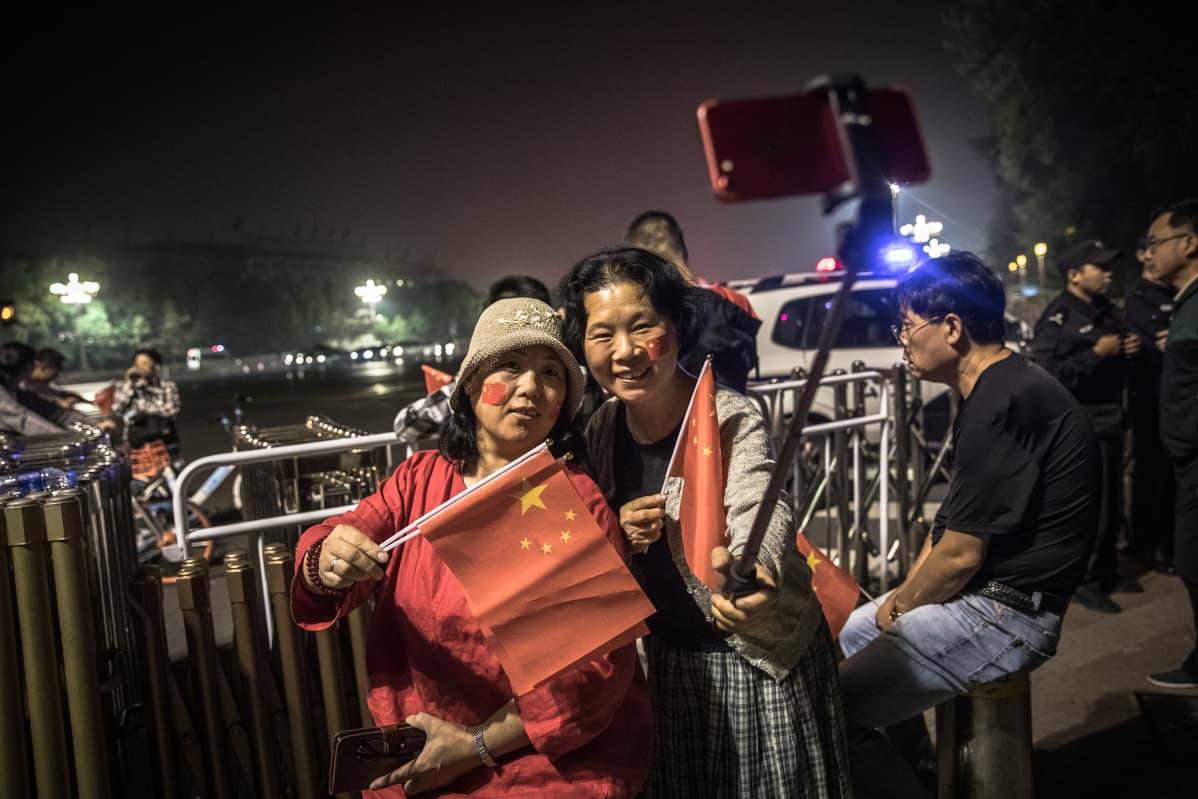 Naiset lipunnostoseremoniassa Pekingissä.