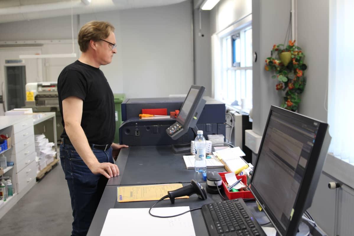 Markprint Oy:n toimitusjohtaja Mikko Ilomäki seuraa näytöltä digipainokoneen toimintaa.