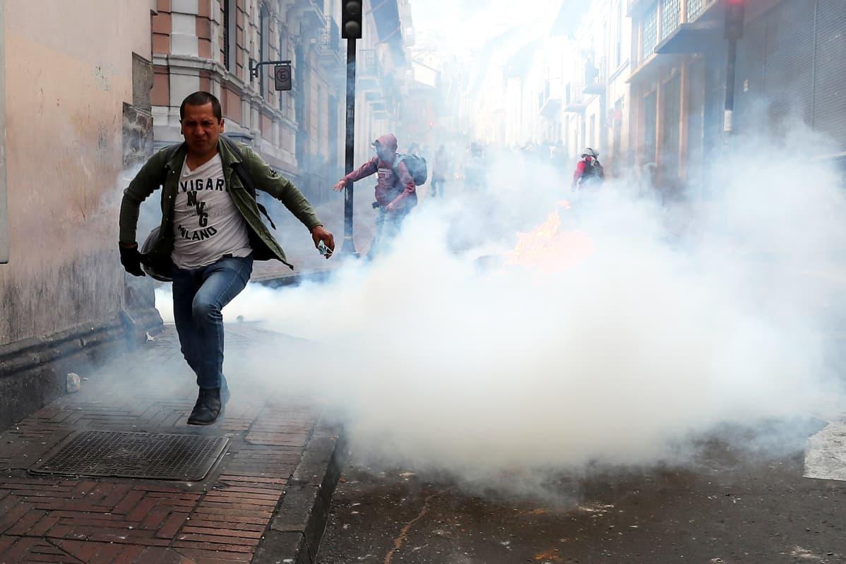 Mies pakenee kyynelkaasusavua Quitossa Ecuadorissa 7. lokakuuta.