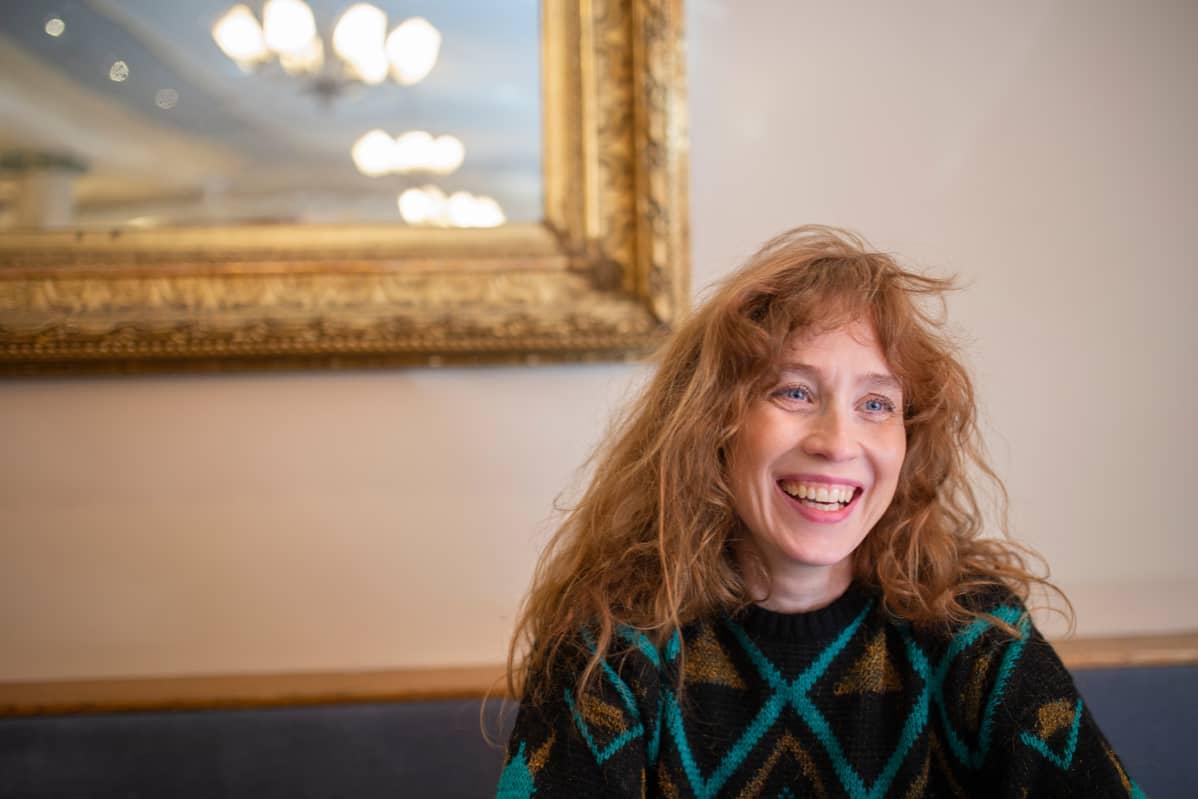 Punahiuksinen nainen nauraa kahvilassa.