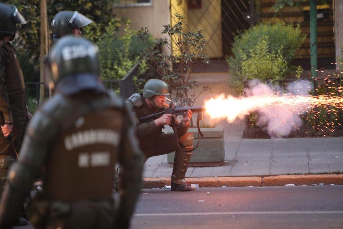 Poliisi ampuu kyynelkaasua Santiagossa Chilessä.