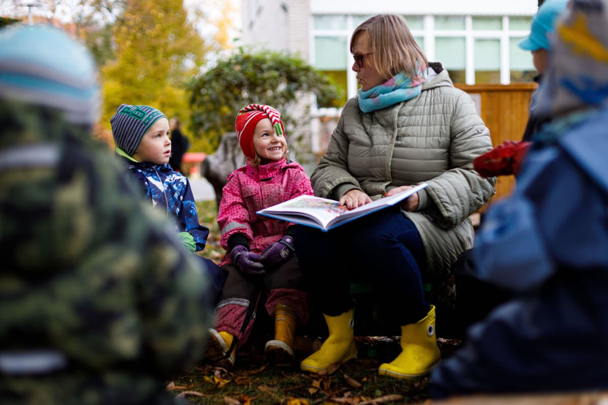 Lastentarhanopettaja Birgitta Tints lukee satua Tammetõrun päiväkodin lapsille. Johannes ja Karin kuuntelevat.