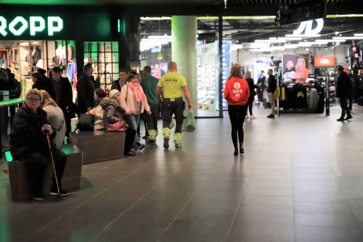 Nuori nainen kerrosoppaana ostoskeskuksen käytävällä.