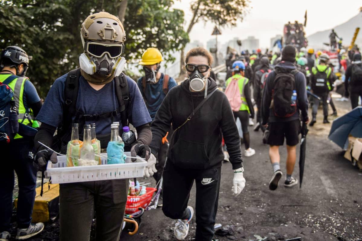 Kypäräpäinen mielenosoittaja kantaa korissa polttopulloja.