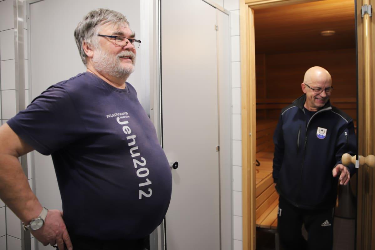 Sysmän VPK:n Asko Nurminen ja Jorma Sainio esittelevät paloaseman sukupuolineutraaleja peseytymistiloja