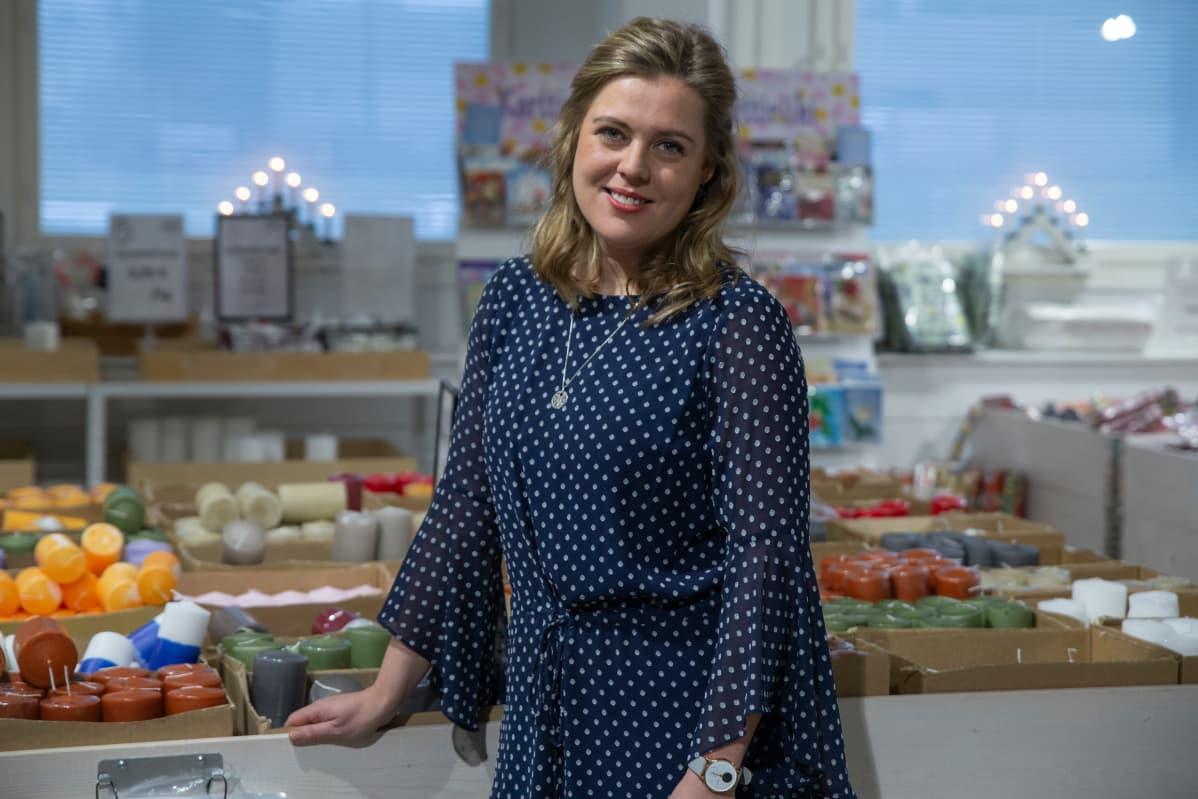 Linda Schlobohm aloitti Suomen vanhimman kynttilätehtaan toimitusjohtajana vajaat kaksi vuotta sitten. Kuvassa hän seisoo Riihimäen tehtaan myymälässä kynttilöiden keskellä.