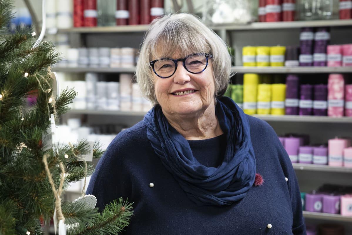 Kynttiläyrittäjä Terttu Kilpinen seisoo hymyillen myymälässään kynttilöiden ympäröimänä.