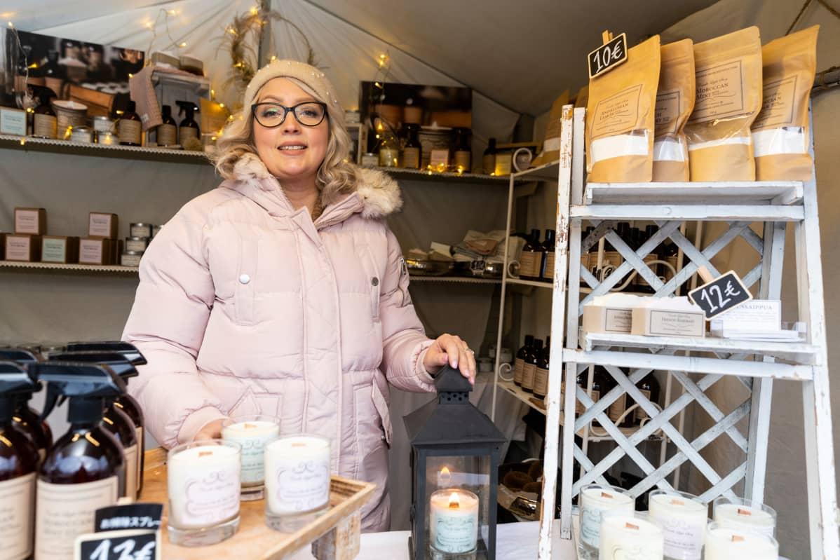Annina Rosenström myyntikojussaan Tuomaan Markkinoilla Helsingissä. Lyhdyssä pöydällä palaa soijavahakynttilä.