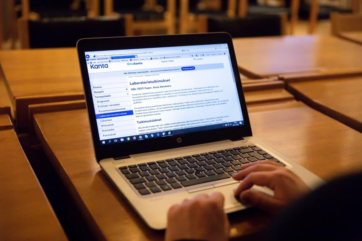 Olan yli kuva naisesta, joka selaa tietokoneella Kelan Omakanta-palvelua.
