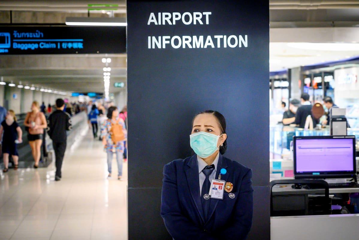 Suojamaskiin pukeutunut lentokenttävirkailija Bangkokin kansainvälisellä lentoasemalla.