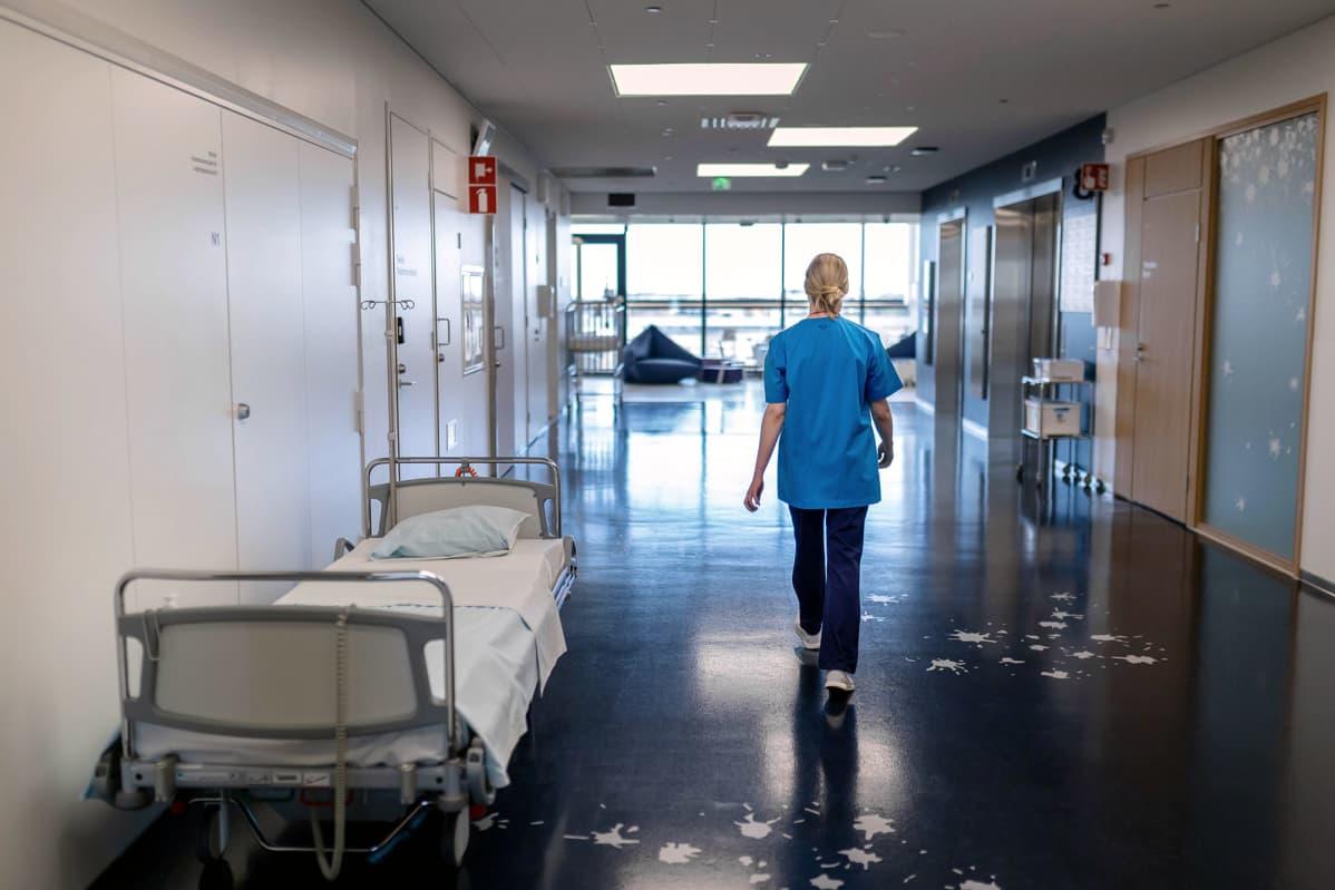 Sairaanhoitaja kävelee sairaalan käytävällä.