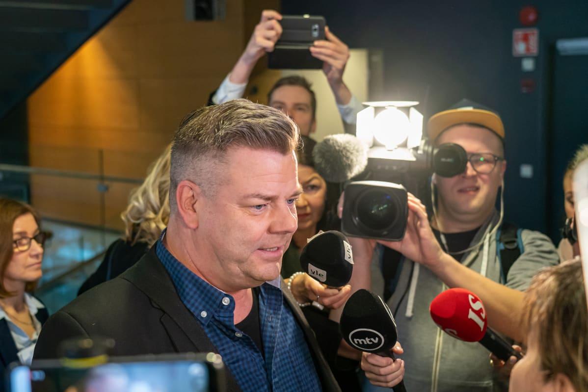 Jari Sillanpää käräjäoikeudessa toimittajien piirittämänä.