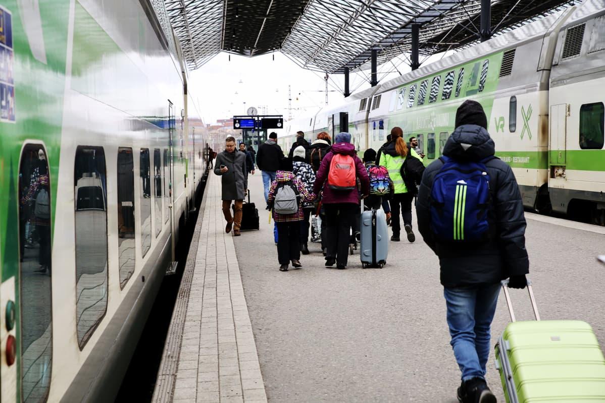 Matkustajia helmikuussa Helsingin rautatieasemalla.